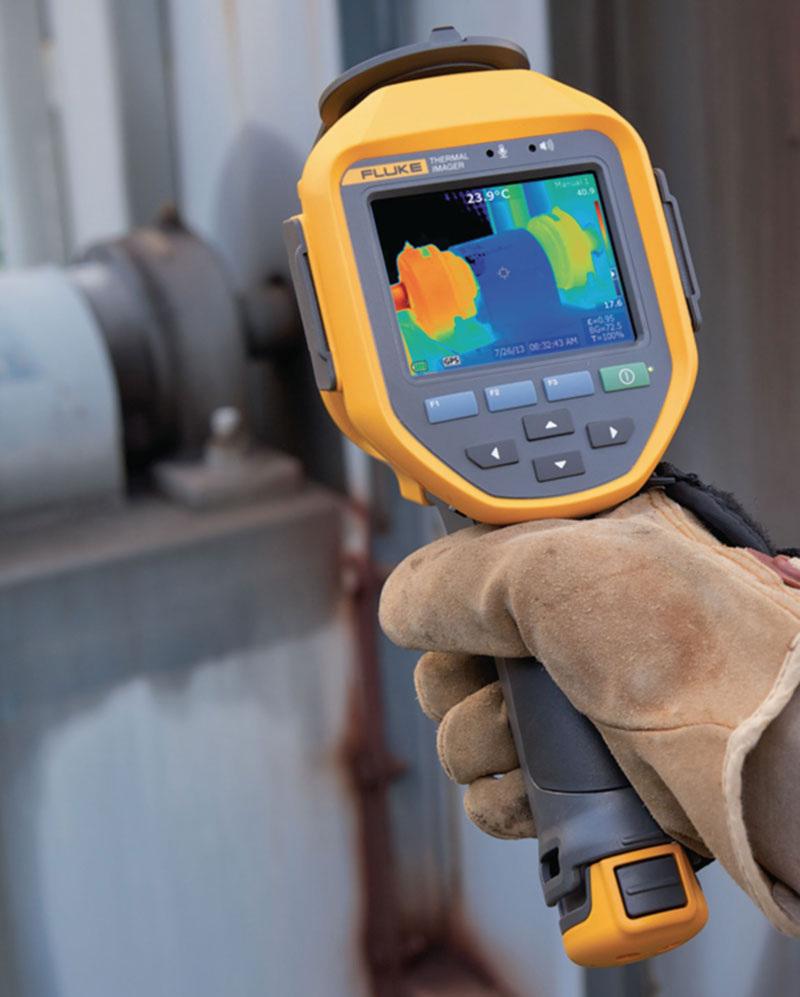 Fluke TI300 thermal imager being held by a gloved hand, aimed at a valve
